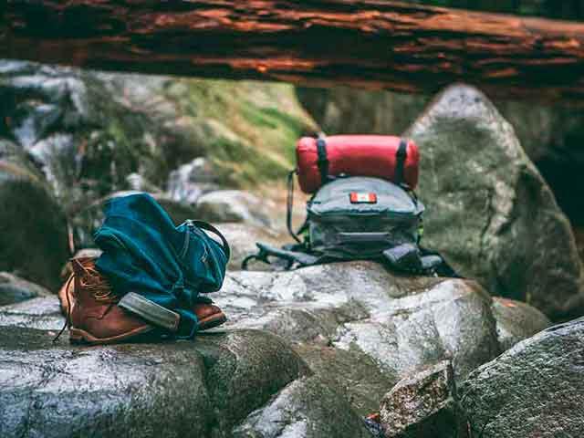 Rucksack und Kleiderbündel in der Natur