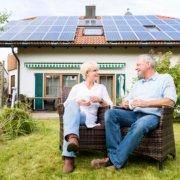 Paar sitzt im Garten von einem Haus